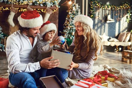 Adult parents with boy in Santa hats gathering at home in Christmas time and opening presents