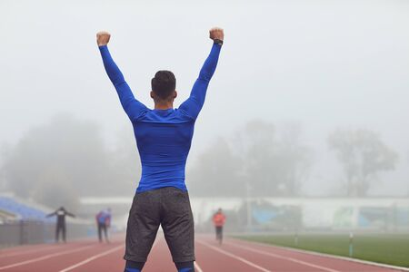The guy the athlete raised his hands up at the stadium in the fog. The concept of victory of success motivation good luck in sports.