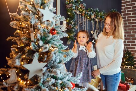 Mother and daughter decorate the Christmas tree in the room. Stock Photo
