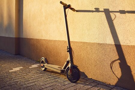 Electric scooter on a background of a wall in the city in the sun.