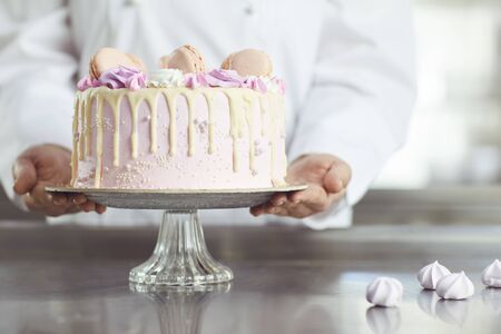 Confectioners hands hold a pink cake in a candy store. Pink cake on the table.
