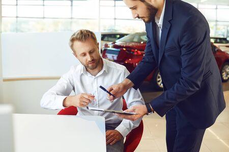 A man buys a car in a car showroom. A man signs a car rental agreement.