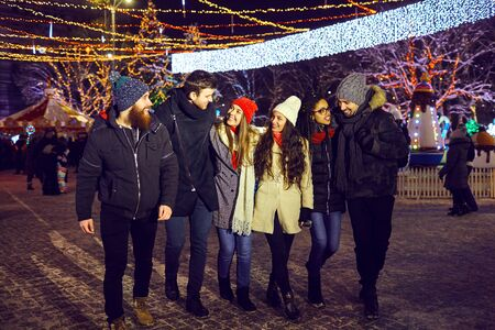 A group of friends have fun walking on Christmas streets at night. Stock Photo