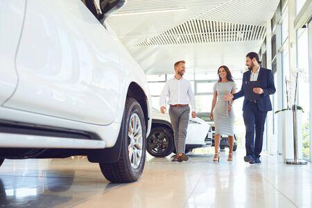 La coppia felice e il concessionario che vendono auto guardano l'auto nello showroom. Acquistare un'auto a noleggio. Archivio Fotografico