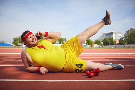 Fat funny man lying on the phone talking on the track at the stadium. Stockfoto