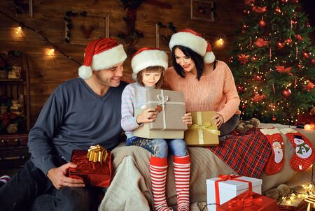 Happy family gives daughter a gift sitting on the bed in the room at Christmas. 写真素材