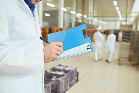 Hands of a person in a white coat make an entry in a folder with papers in a warehouse. Accounting for goods in warehouse.