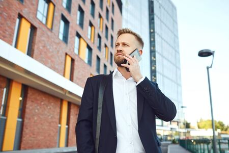 Businessman talking on the phone on the background of business building.