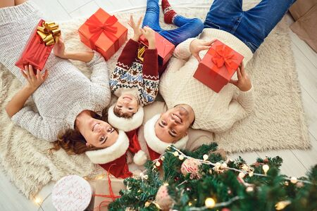 From above view of cheerful parents with boy in Santa hats lying on cozy floor near Christmas tree holding presents and looking at camera