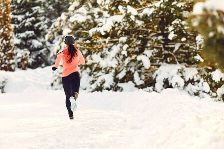 Athletic girl jogging in the snow on the nature in winter