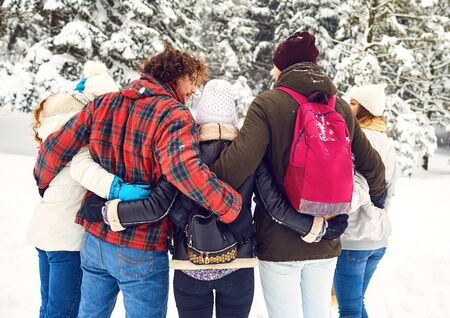 Friends embracing in the woods in winter from the back