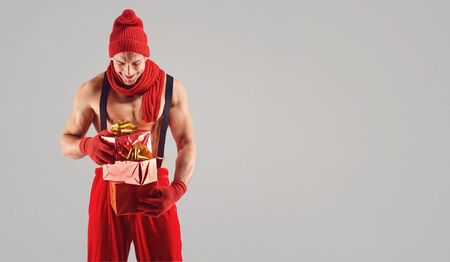 Man athlete with gifts in hand in Christmas on a gray background. Stok Fotoğraf