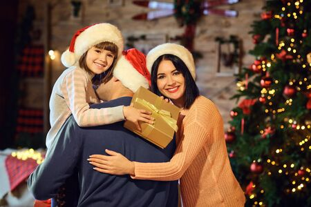 A happy family is embracing in a room for Christmas.