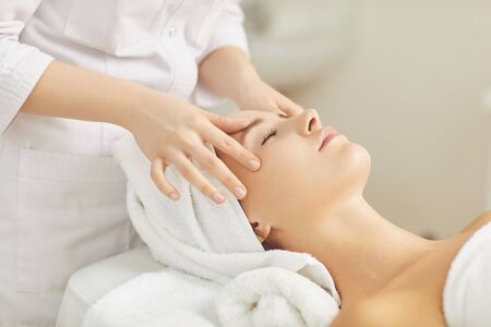 Beautician makes facial massage to the girl in the cosmetology office. Stock Photo