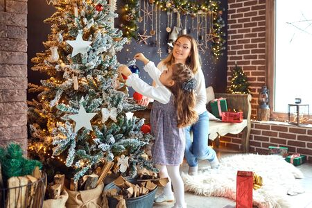 Mother and daughter decorate the Christmas tree in the room. Stock fotó