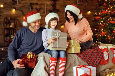 Happy family gives daughter a gift sitting on the bed in the room at Christmas. Фото со стока