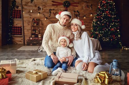 Happy family smiling at home with christmas tree