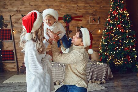 Parents play with their son on the bed in the room at Christmas. Father and mother throws up a fun boy at Christmas. Фото со стока