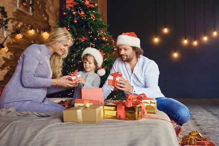 Parents gives a child a gift box in the house at Christmas Фото со стока