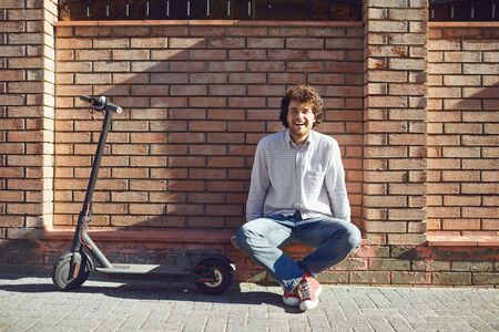 Il giovane in un casco guida uno scooter elettrico su una strada cittadina in estate.