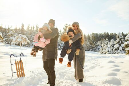 Woman and man with children having fun in winter forest playing with snow in sunlight