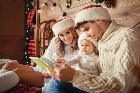 Happy family reading a book while sitting on the bed at Christmas.