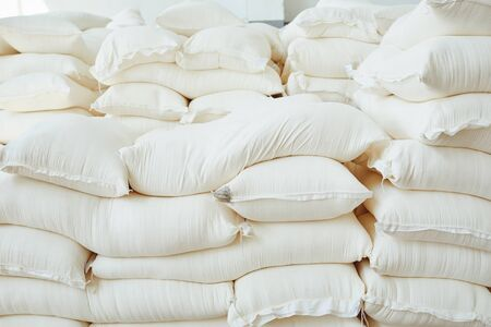 Many white bags in warehouse. Bags of rice sugar flour corn cement in storage.