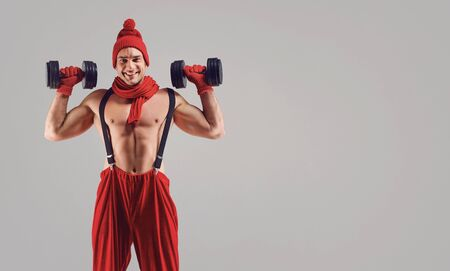 A man with a muscular figure in a red hat and a scarf with dumbbells in his hands on a gray background. Stock Photo