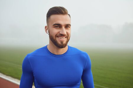A sports guy in blue clothes smiles while looking at the stadium in the fog. Stock fotó