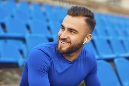 A guy in sportswear is sitting in the stadium after training. Athletic healthy lifestyle Stock fotó