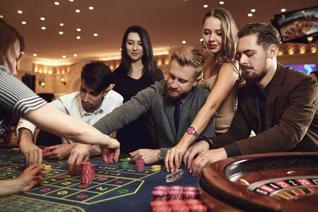 Happy people are betting in gambling at roulette poker in a casino.