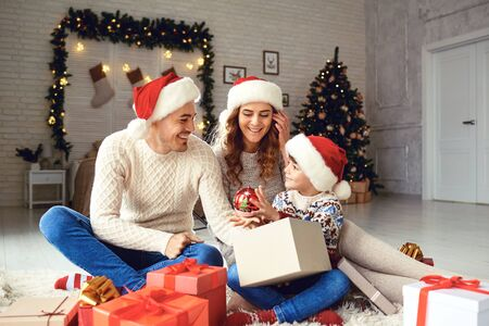 The family gives boxes of gifts to the child sitting on the floor at home for Christmas.
