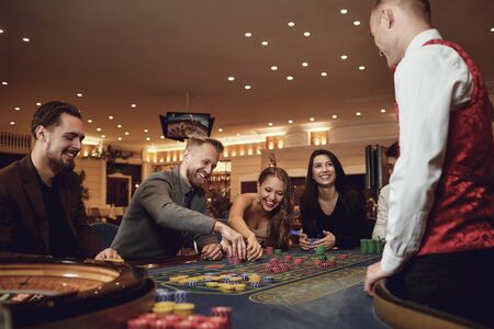 Happy people are betting in gambling at roulette poker in a casino. Gambling betting in casino concept.