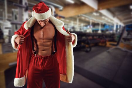 Santa with an athletic body on the background of the gym.