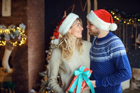 Husband and wife with poadrkami in a room with a Christmas tree and fireplace. Stock Photo
