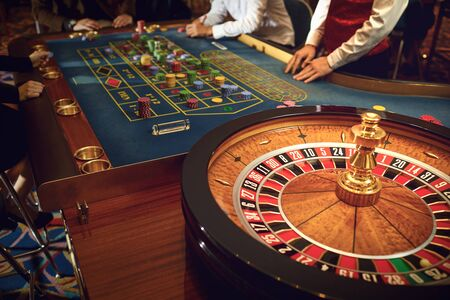 People gambling at roulette poker table in a casino.