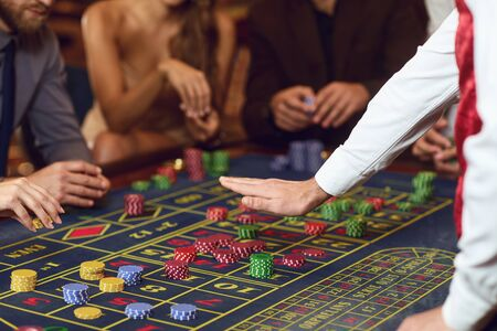 People gambling at roulette poker in a casino. Croupier's hand gesture on the table with roulette chips. 版權商用圖片