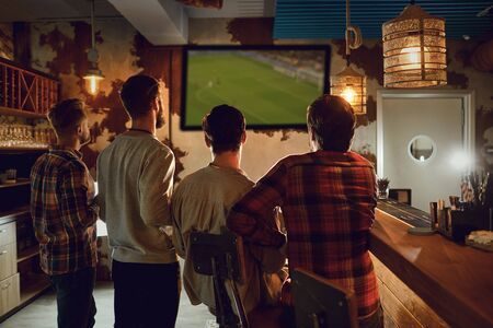 A group of people watching tv football in a sports bar. Fans cheerfully cheer in a restaurant, drink beer. Фото со стока