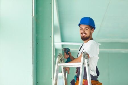 A builder standing on a ladder installs drywall at a construction site inside an office. Banque d'images - 137127434