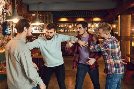 Men fight in a pub bar. Drunk people are fighting in a pub. Banque d'images - 137127439