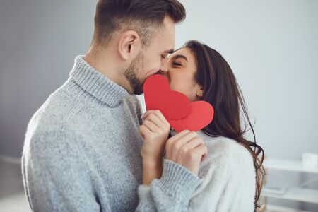 Valentines day. Loving couple with hearts in hand kisses in the room. Banque d'images - 137127442