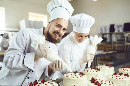 Confectioners with a bag for the cream will decorate the cake in the pastry shop. Imagens