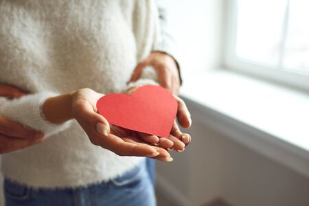 Red heart in the hands of a couple in love. St. Valentines Day. Stock Photo - 137127448
