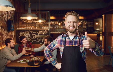 Bearded waiter barista bartender standing against the background of the pub bar. Banque d'images - 137127449