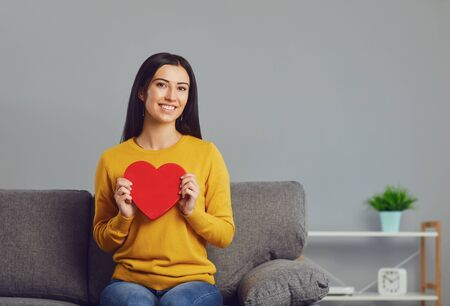 Beautiful girl holding a red heart in her hands while sitting on a sofa in a gray room. Valentines day. Banque d'images - 137127459