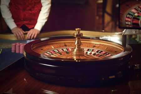 Gambling roulette table in a casino. Concept betting game gambling casino roulette croupier background. Banque d'images - 137127477