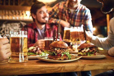 Burger with beer on the table of a group of friends in a bar pub. Hamburger on the background of people in a restaurant. Banque d'images - 137127479