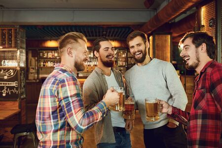 Group of happy friends clinking glasses with beer at a sports bar in a pub restaurant. Banque d'images - 137127482