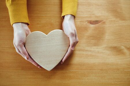 Valentines day. Wooden heart in the hands of a girl on the table. Banque d'images - 137129650