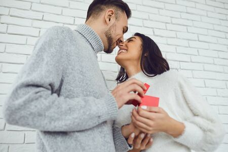 The guy makes a marriage proposal to the girl. Smiling man gives a marriage proposal ring on a white brick background. Banque d'images - 137129651